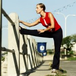 Young Woman Stretching Against a Railing